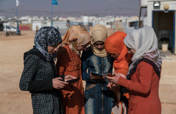 Adolescent girls use cellphones and tablets in the Za'atari camp for Syrian refugees